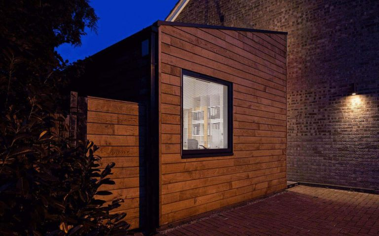 Dusk view of modern timber clad annexe extension by Tait Architects Berkshire